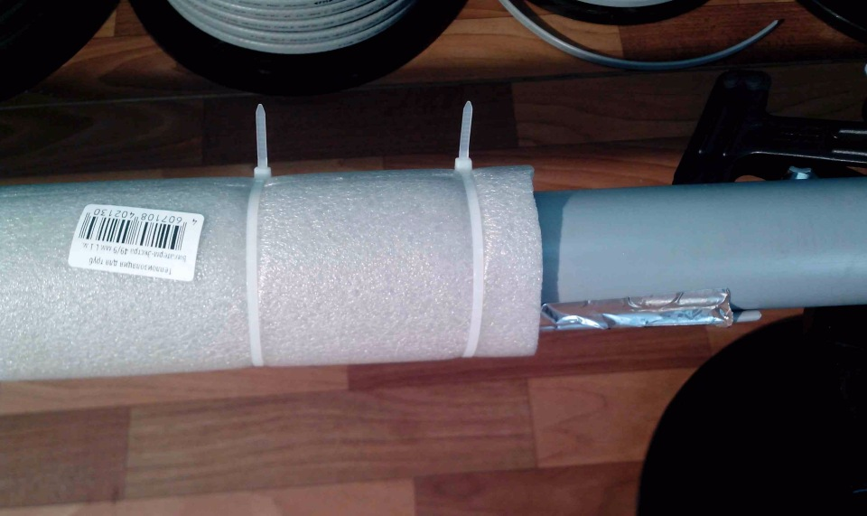 На фото — утепленная канализационная труба с приклеенным алюминиевым скотчем греющим кабелем