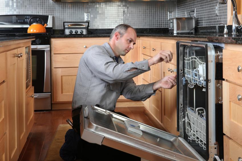 Мужчина настраивает посудомоечную машину