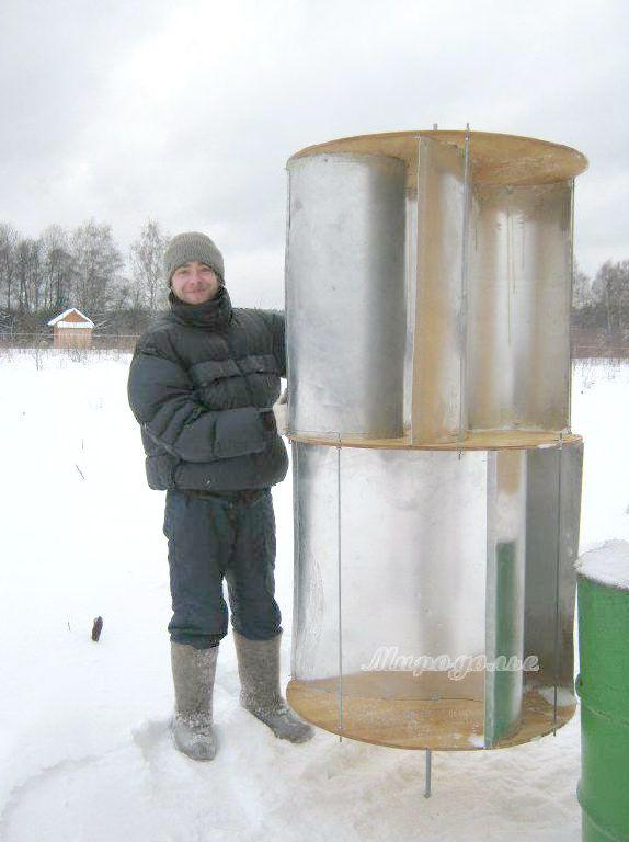 Вертикальный ветрогенератор на земле рядом парень в валенках